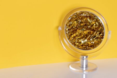 Closeup of a transparent round cosmetic mirror with selective focus on the centre of the magnified reflection of a golden metallic sparkling tinsel over yellow background. Space left side. Macro.
