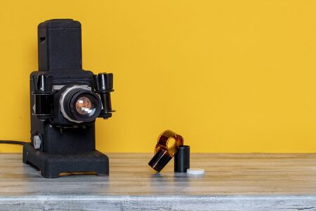 Close-up of a running old black projector for viewing slides and filmstripes and a negative color film on table over yellow background. Entertainment last century to look holiday pictures on a projection screen. Macro.