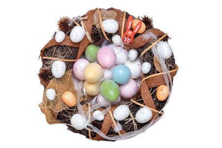 Happy easter decorations background. Top view on colorful festive easter eggs wreath with a large number of various eggs and a wooden bunny. Beautiful decoration element. Religion and culture concept.