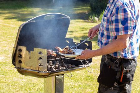 A man at the charcoal grill is grilling steaks, grill sausages and chicken wings and using barbecue tongs. Selective focus on the grill against a green lawn background on a sunny spring day. BBQ concept. Macro. Stock Photo