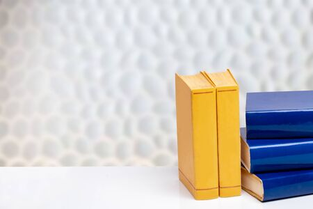 Books backgrounds. Close-up of a stack blue and yellow books on a white table in front of abstract blurred bright background. Space for text and montage.