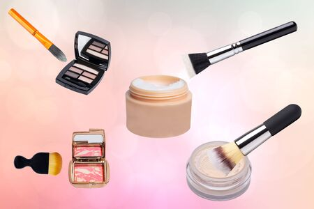 Decorative composition of colorful beauty and makeup products and tools such as powder, cream and brushes on a abstract light pink background. Advertising beauty and makeup products. Archivio Fotografico
