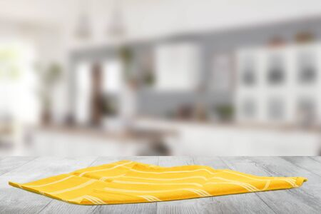 Closeup of a empty yellow striped tablecloth or napkin on a bright rustic wooden table against abstract blurred kittchen background. Template for food and product display montage. Stock Photo