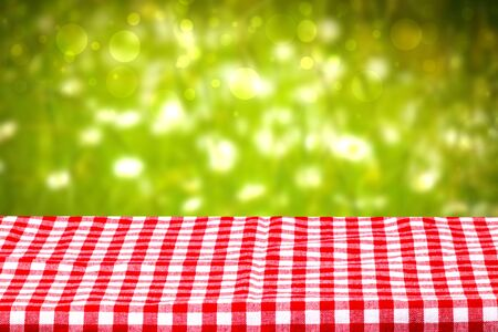 Empty table background. Empty wooden deck table covered with a red checkered tablecloth in front of abstract blurred fresh colorful green summer backdrop. Space for your food and product display montage.