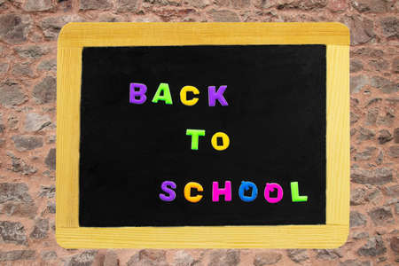 Back to school text written with colorful letters on blackboard. School board on a wall background. Concept of education. 스톡 콘텐츠