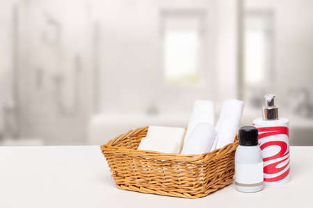 Basket with bath accessories such as soap bars, cream and cosmetic tissues for body care on a white table over blurred bathroom background with copy space. For your product display assembly.