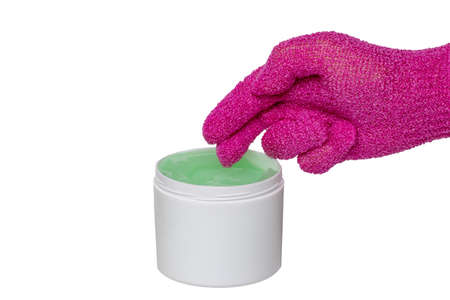 Closeup of an open container with cooling gel (horse balm) for sports injuries and a pink massage glove isolated on a white background. The hand wants to take some gel to start the massage. Banque d'images
