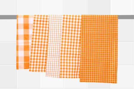 Closeup of various yellow checkered kitchen towels hang on a clothes rail against blurred bright tile background.