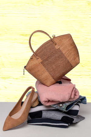 A stack of folded sweaters, a pair of jeans and a trendy brown handbag on top and an elegant brown shoe on table over bright background. Advertising for fashion and accessories.