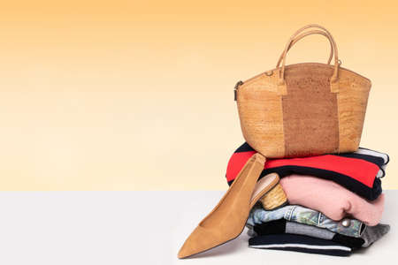 A fashionable brown luxury oak cork women's handbag on a pile of folded women's clothing and a single shoe on the table over light background. Advertising for fashion and accessories.