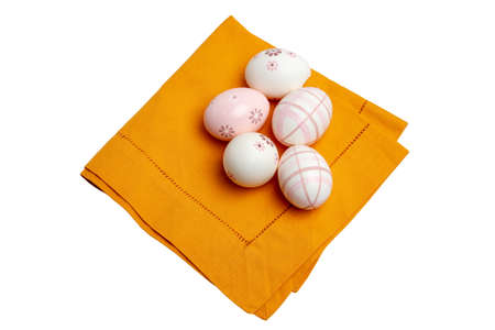 Easter decoration element. Closeup of a yellow kitchen cloth or napkin with five painted easter eggs on it isolated on white. Clipping path. Macro.