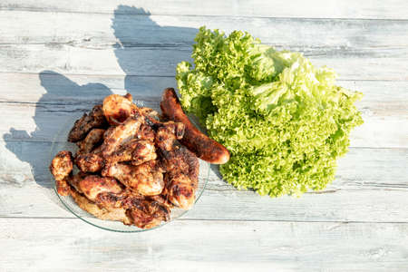 Top view on a glass dish of freshly grilled chicken and sausages surrounded by fresh green salad on a rustic outdoor table. Advertising. Space.