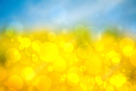 Hello spring background. Abstract bright spring or summer landscape texture with natural yellow bokeh lights and sunshine on blue sky. Beautiful backdrop with space. 免版税图像