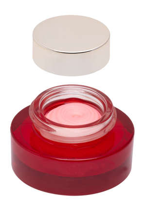 Closeup of an open cosmetic jar of rose concealer cream, makeup foundation, moisturizing cream for the face or an other beauty or make-up product isolated on a white background. Space for label. 免版税图像