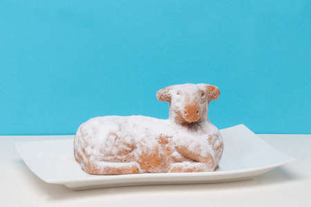Easter card template. A traditional Easter lamb cake on a white plate on a bright glittering table against blue background. Space for design. 免版税图像