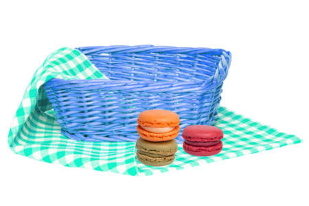 Closeup of an empty wicker basket and three macaron on a green white checkered napkin, blanket or tablecloth isolated on a white background. For your food and product display assembly. Macro.