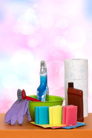 Spring cleaning background. Close-up of house cleaning products and cleaning supplies on orange wooden table over abstract bright background. Household chore concept. Macro. 免版税图像