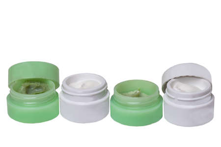 Cosmetic products. Close-up of four opened green and white plastic jars with face cream isolated on a white background. Advertising spa, make-up and beauty. Macro.