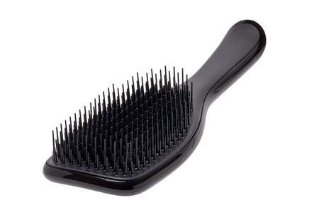 Closeup of a stylish new black hair brush isolated on white background. Concept of body and beauty care. Clipping path. Macro.
