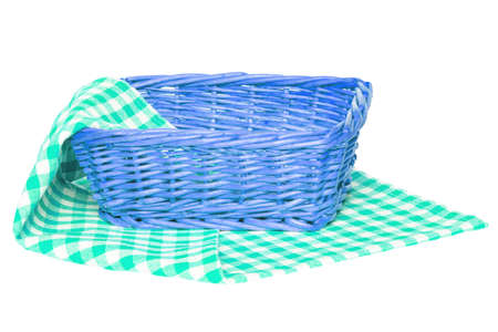 Empty picnic basket. Closeup of an empty wicker basket on a green white checkered napkin, blanket or tablecloth isolated on a white background. For your food and product display assembly. Macro.