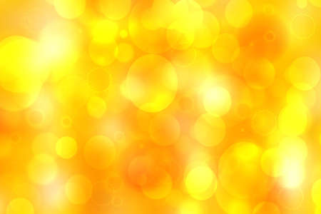 A festive abstract delicate golden yellow orange gradient background texture with glitter defocused sparkle bokeh circles. Card concept for Happy New Year, party invitation, valentine or other holidays.