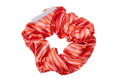 Fashionable hair band. Close-up of an gold orange striped silk scrunchy for ponytail hairstyle isolated on a white background. Accessories for woman or girl.