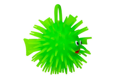 Rubber toys. Funny green puffer fish made of rubber. Cute toy fish isolated on a white background. Macro.