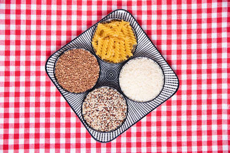 Vegetable food. A decorative plate with four bowls with buckwheat, noodles, rice and quinoa on a red checkered tablecloth. Healthy eating. Top view with space for design.