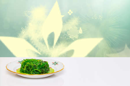 Japanese food. Fresh chuka salad with sesame on plate on white table in front of abstract green lighted underwater world. Template for your product display montage. Health concept. 免版税图像