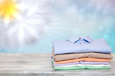 Stack of colorful clothes. Pile of folded cotton shirts on a bright table with space for your display product montage against abstract blurred natural light sunny background. Summer fashion.