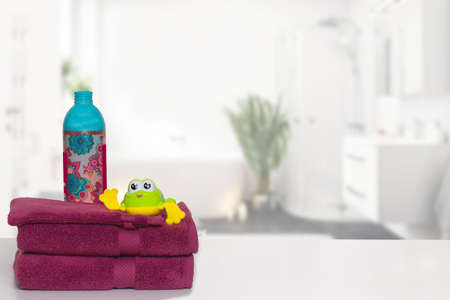 Table top on towels background. Closeup of a stack or pile of violet soft terry bath towels with a wash softener and a funny frog over blurred bathroom background with copy space. For your product display assembly.