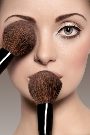 Portrait of a beautiful woman with a make up brush Stock Photo - 10018232