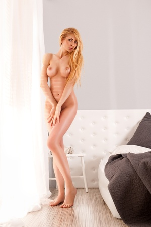 Beautiful, naked woman posing next to the window
