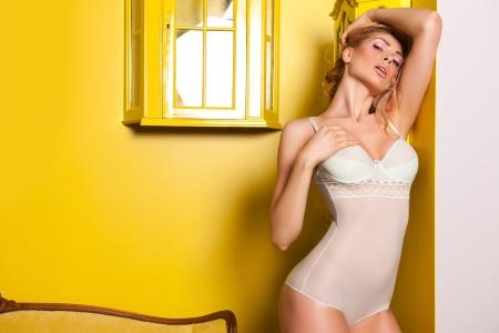 Beautiful woman posing in a yellow interior