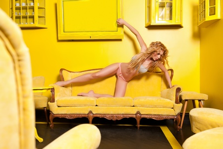Beautiful woman posing in a yellow interior photo