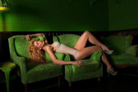 Beautiful, sexy woman in a dark, green room
