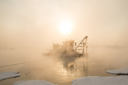 clarifier: a dredger boat in winter mist at sunset Stock Photo