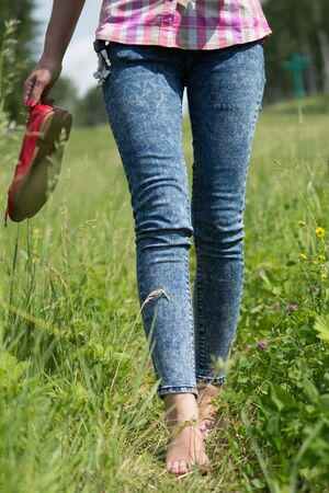 shoeless: Beautiful young female legs walking on the grass in summer