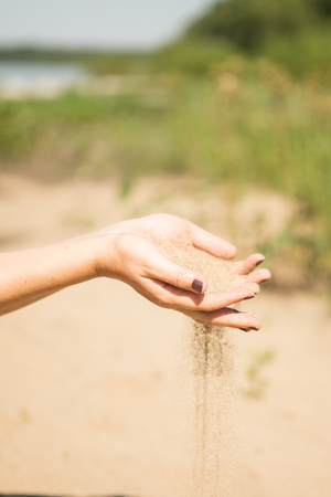 sand running through hands of woman Stock Photo