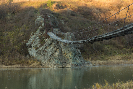 The very old hanging footbridge across a small river.