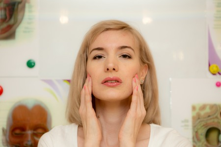 facial gymnastics. the girl does massage and rejuvenating exercises for the face Stock Photo