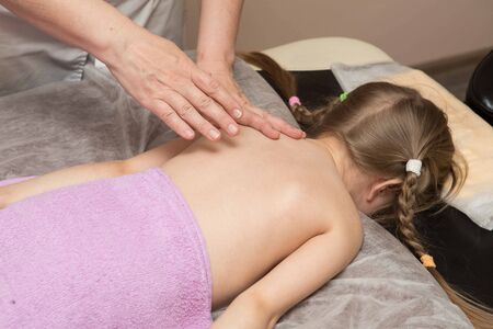 the masseur gives the child a back massage, the girl clearly enjoys it