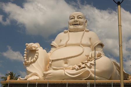 Big laughing sitting Buddha in Vinh Trang Pagoda in South Vietnam Standard-Bild