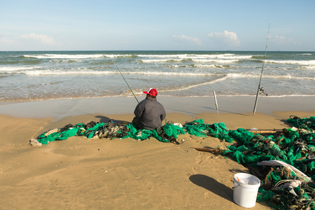 The fisherman sits and fishes on the beach.Cam Ranh Vietnam Stock Photo