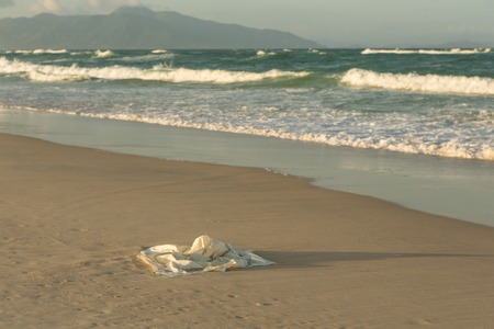 Plastic garbage on the beach in the sea, plastic bag pollutes the sea
