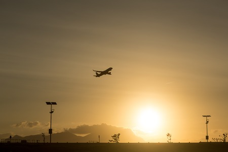 Silhouette of a plane taking off from the airport at sunset airport Stock Photo