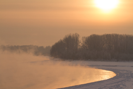 winter frosty sunset on the river in Siberia in winter in December