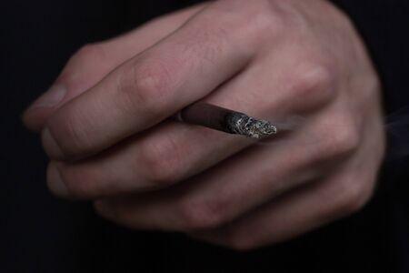 Smoldering cigarette in hand on a dark background. Smoke. Standard-Bild
