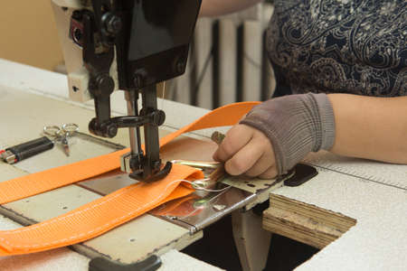 Industrial sewing machine sews a webbing sling. Manufacture of textile slings and tie straps 版權商用圖片