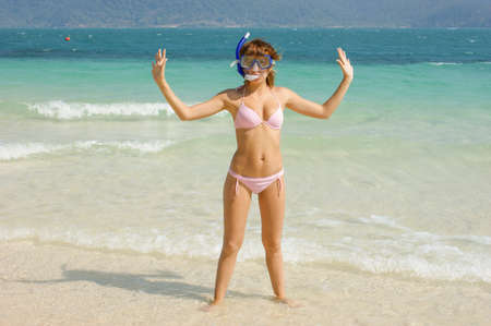 Young beautiful girl with a diving mask on a tropical island-happy tourist on vacation